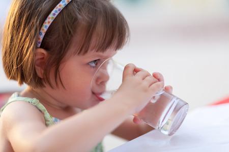 puros: Niña linda que bebe al aire libre de agua - profundidad de campo muy baja (niña
