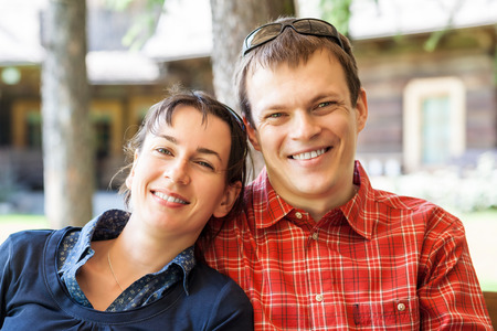 Cheerful couple sitting in front of a new wooden house Stock Photo