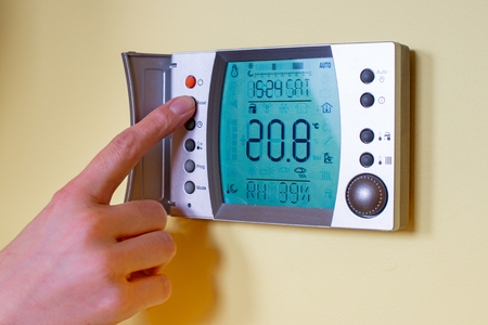 programmable: Closeup of a womans hand setting the room temperature on a modern programmable thermostat. Save energy and money concept