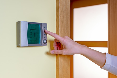 reducing: Closeup of a womans hand setting the room temperature on a modern programmable thermostat - with copy space. Save energy and money concept
