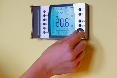 save heating costs: Closeup of a womans hand setting the room temperature on a modern programmable thermostat. Save energy and money concept
