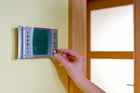 save heating costs: Closeup of a womans hand setting the room temperature on a modern programmable thermostat - with copy space. Save energy and money concept