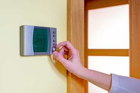 programmable: Closeup of a womans hand setting the room temperature on a modern programmable thermostat - with copy space. Save energy and money concept