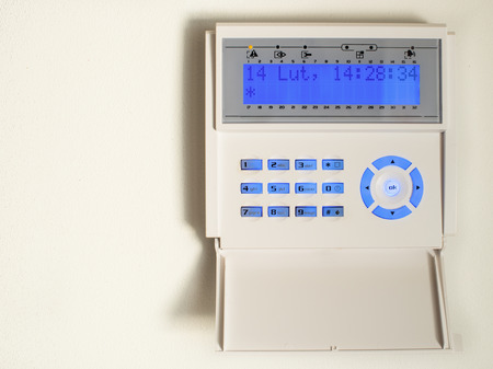 Home security alarm system activated on white wall background