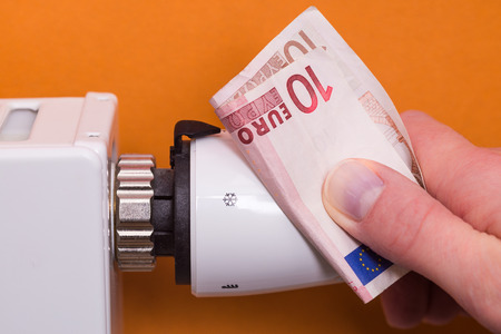 conform: Close-up Of Female Hand Adjusting Thermostat Covered With Banknote