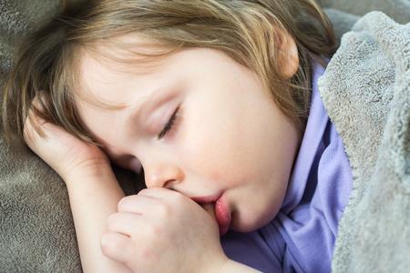 Sleeping little cute baby sucking thumb 写真素材