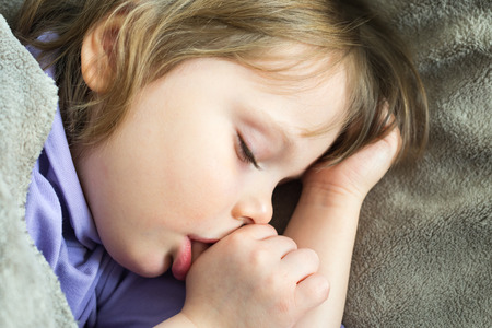sucking: Sleeping little cute baby sucking thumb Stock Photo