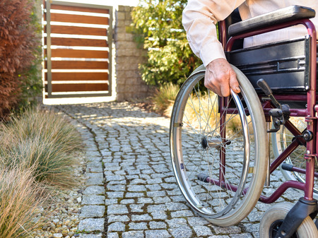 Close-up of old male hand on wheel of wheelchair during walk in park