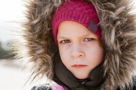 fur hood: portrait of serious girl wearing fur hood looking at camera outdoor