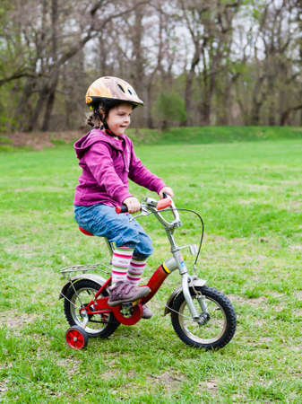 little girl learning to ride a bicycle with training wheels Standard-Bild