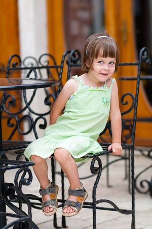 peekaboo: Peekaboo girl. Cute little girl playing peekaboo sitting at coffee table outdoors. Shallow depth of field. Creamy background