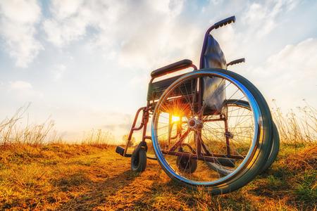 persona en silla de ruedas: Silla vacía en la pradera al atardecer. Concepto de milagro. Persona sanada levantó y se fue