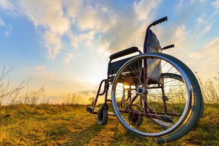 persona en silla de ruedas: Silla vac�a en la pradera al atardecer. Concepto de milagro. Persona sanada levant� y se fue