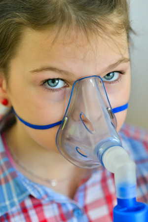 exhalation: Girl with asthma inhaler. Girl with asthma problems making inhalation with mask on her face. Inhalation treatment of respiratory diseases. Stock Photo