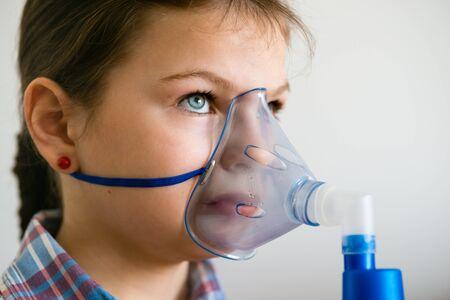 ox�geno: Chica con inhalador para el asma. Chica con problemas de asma que la inhalaci�n con m�scara en su rostro. Inhalaci�n tratamiento de enfermedades respiratorias.