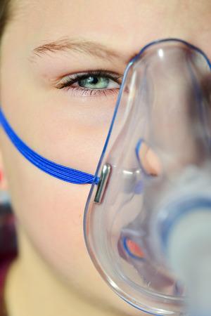 asthma: Chica con inhalador para el asma. Chica con problemas de asma que la inhalación con máscara en su rostro. Inhalación tratamiento de enfermedades respiratorias.