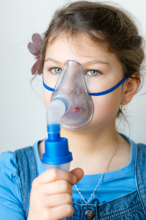 inhale: Girl with asthma inhaler. Girl with asthma problems making inhalation with mask on her face. Inhalation treatment of respiratory diseases. Stock Photo