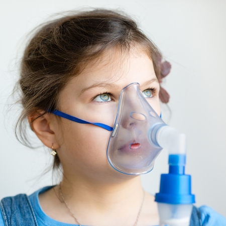 Girl with asthma inhaler. Girl with asthma problems making inhalation with mask on her face. Inhalation treatment of respiratory diseases. Stock Photo
