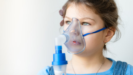 asthma: Girl with asthma inhaler. Girl with asthma problems making inhalation with mask on her face. Inhalation treatment of respiratory diseases. Stock Photo