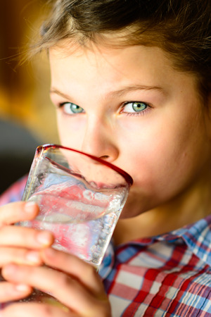 purify: Girl drinking water. Cute little girl drinking water - very shallow deep of field Stock Photo