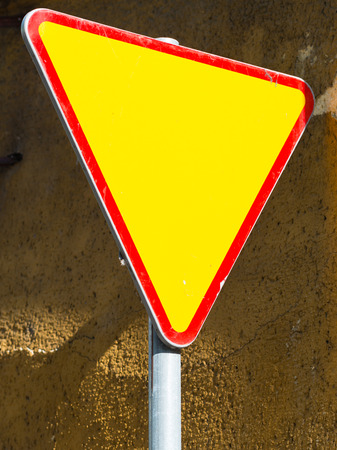 yield: Give way sign - yield sign - against rough  mustard wall background Stock Photo