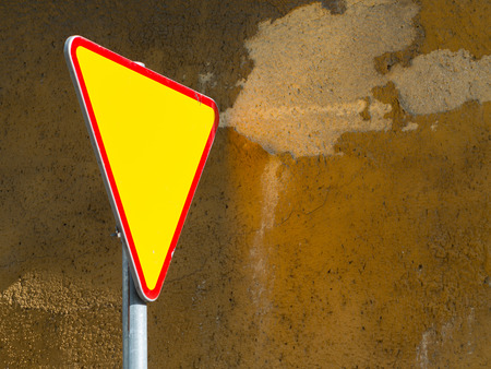 yield sign: Give way sign - yield sign - against rough  mustard wall background Stock Photo