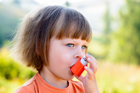 Girl Using Inhaler on a sunny day - to Treat Asthma Attack.  Inhalation treatment of respiratory diseases. Shallow depth of field. Allergy concept.
