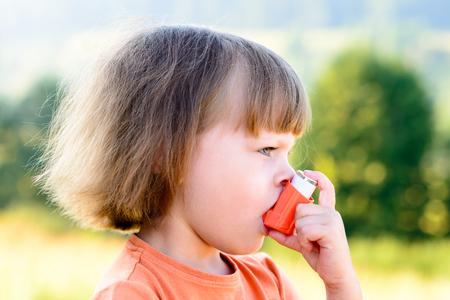 asma: Chica que usa el inhalador en un d�a soleado - para tratar el ataque de asma. Inhalaci�n tratamiento de enfermedades respiratorias. Poca profundidad de campo. Concepto de alergia.