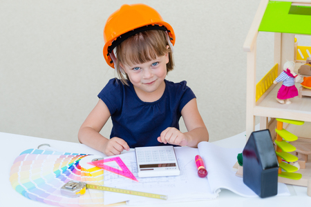 dollhouse: Childhood, Construction, Architecture, Home Improvement, Developing,  Home Improvement and people concept - cute smiling little girl in orange protective helmet - playing engineer or builder