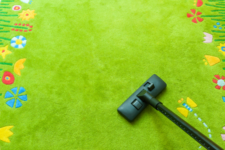green carpet: Vacuum cleaner cleans carpet, with copy space for text message, advertising - Spring Cleaning Concept