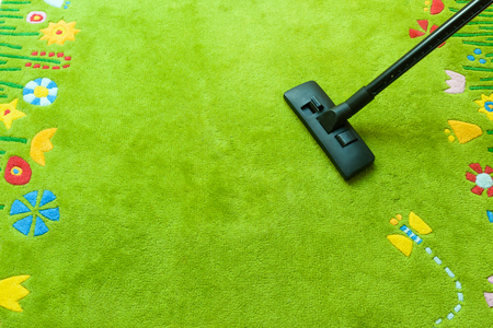spring cleaning: Vacuum cleaner cleans carpet, with copy space for text message, advertising - Spring Cleaning Concept