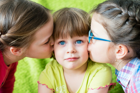 embarrassed: Embarrassed girl looking at camera. Toddler girl being kissed by two sisters. Stock Photo