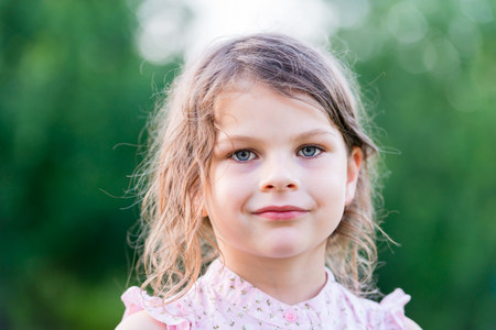 Serious girl. Cute little girl looking at camera. Closeup portrait with shallow depth of field.