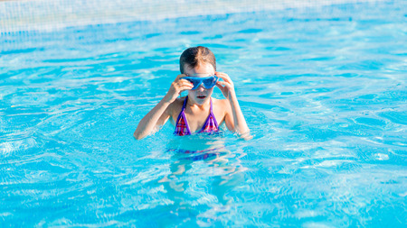 girl glasses: Cute happy young girl in blue goggles swimming and snorking in the swimming pool Stock Photo