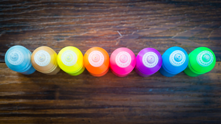 pigments: Bottles with colorful dry pigments on wooden background - rainbow colors