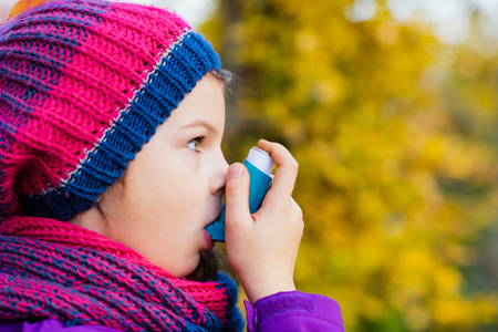 asthma: Girl Using Inhaler on a autumn day - to Treat Asthma Attack. Inhalation treatment of respiratory diseases. Shallow depth of field. Allergy concept. Stock Photo