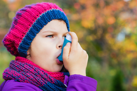Girl Using Inhaler on a autumn day - to Treat Asthma Attack. Inhalation treatment of respiratory diseases. Shallow depth of field. Allergy concept. Banque d'images