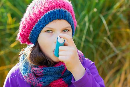 ni�os sanos: Chica que usa el inhalador en un d�a de oto�o - para tratar el ataque de asma. Inhalaci�n tratamiento de enfermedades respiratorias. Poca profundidad de campo. Concepto de alergia. Foto de archivo