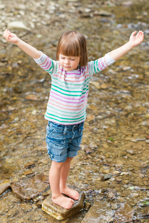 Cute little barefoot girl praying - standing in a mountain stream
