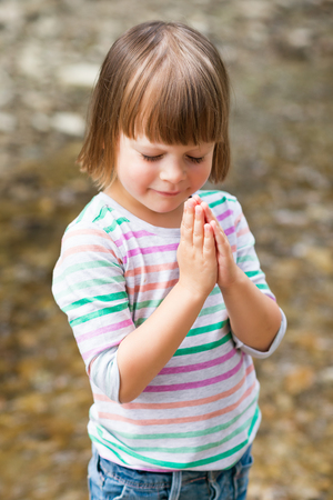 head in hands: Cute little girl praying over textured background