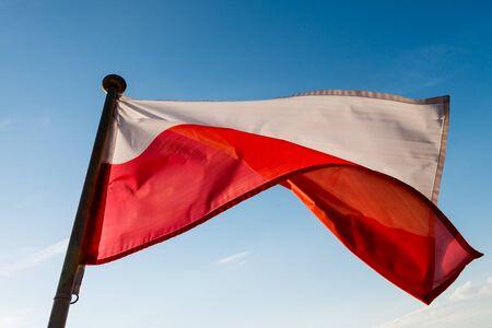 polish flag: Polish flag on the mast against blue sky Stock Photo