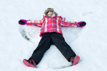 snow white: Little girl laying on snow and making - Snow Angel. Child smiling and spreading hands and feet - winter fun Stock Photo