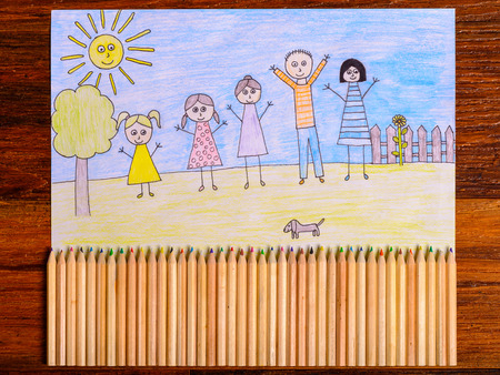crayon drawing: Happy family drawing - kids crayon drawing on wooden table with crayons forming fence
