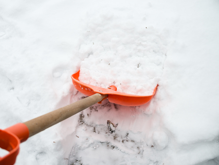 wintery day: Snow removal. Orange Shovel in snow, ready for snow removal, outdoors. Stock Photo