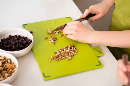 Chopping walnuts on a cutting board with a knife - preparing granola in kitchen at home