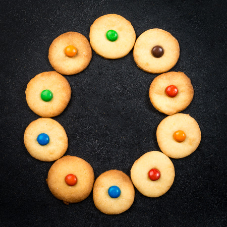 bake sale sign: Cookie alphabet - Homemade child cookies - O letter of the alphabet - black stone background
