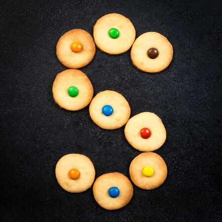 bake sale sign: Cookie alphabet - Homemade child cookies - S letter of the alphabet - black stone background