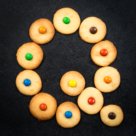 bake sale sign: Cookie alphabet - Homemade child cookies - Q letter of the alphabet - black stone background