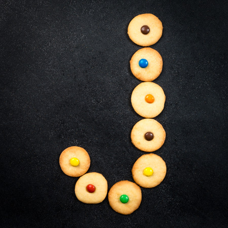 bake sale sign: Cookie alphabet - Homemade child cookies - J letter of the alphabet - black stone background Stock Photo