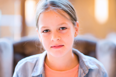 boca cerrada: Retrato de la muchacha joven y bonita sonrisa con la boca cerrada sentado en el sillón - muy poca profundidad de campo